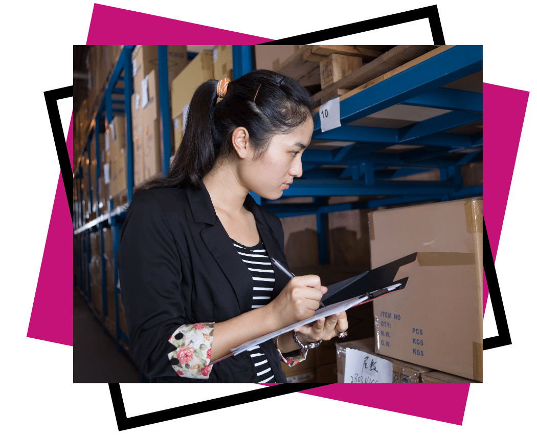 human resources framework - exceler8 - Image of a lady with dark hair standing in a warehouse next to boxes. She has a clipboard and pen in her hand.