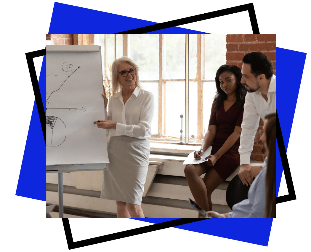 team building and workplace culture - exceler8 - Image of a lady with blonde hair presenting to her younger team.