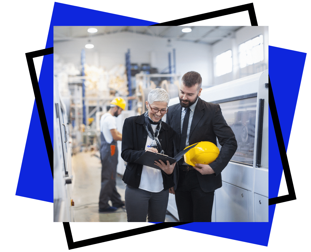 team building and workplace culture - exceler8 (3) - Image of a lady with grey hair talking to a main in a factory in a suit. He has a hard hat under his arm and she has a clipboard